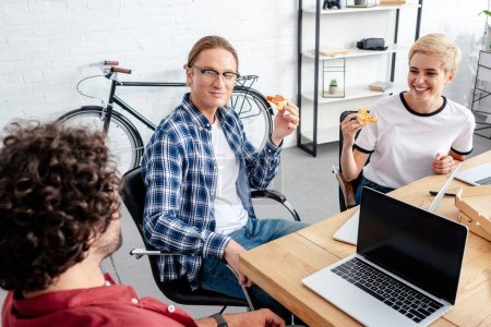 high angle view of smiling young coworkers eating pizza together while working together in office