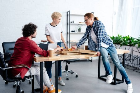 young coworkers eating pizza together while working together in office