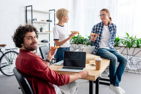 young start up team eating pizza together while working in office