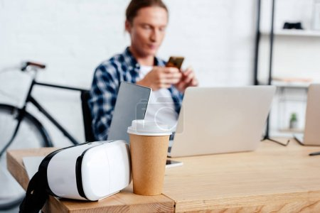close-up view of coffee to go, virtual reality headset and man using smartphone behind