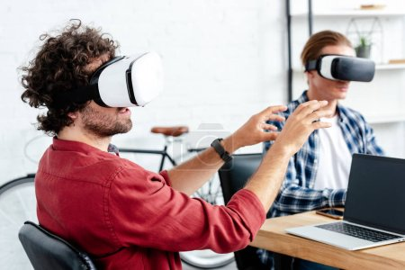 young men in virtual reality headsets working together in office