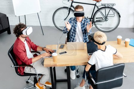high angle view young colleagues in virtual reality headsets using laptops