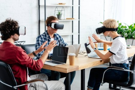 young colleagues using virtual reality headsets and laptops while working together