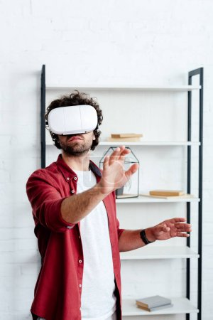 young man using virtual reality headset in office