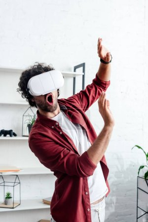 excited young man using virtual reality headset in office