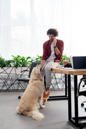 smiling young man talking by smartphone and looking at dog in office