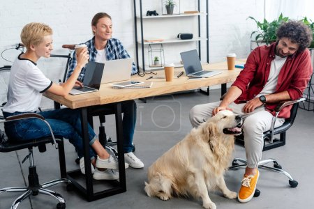 smiling young people looking at colleague stroking dog in office