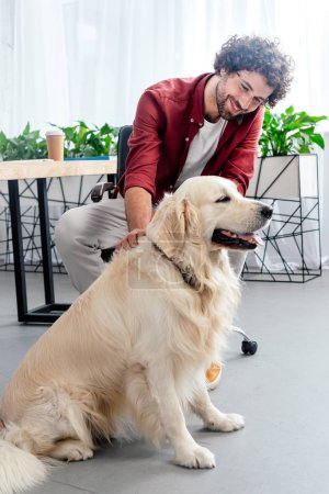 smiling young man stroking dog at workplace