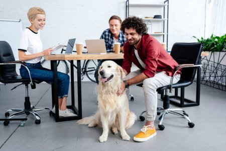smiling young business people looking at dog while working in office