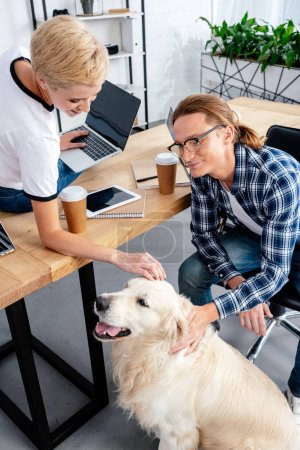smiling young coworkers stroking labrador dog at workplace