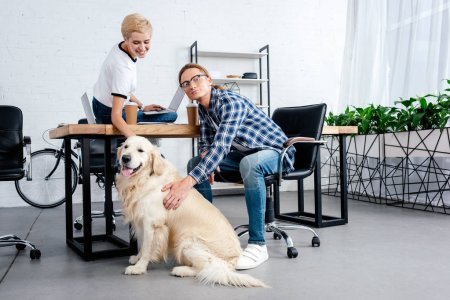 smiling young coworkers stroking dog at workplace
