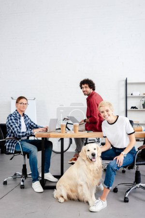 young start up team and dog looking at camera while working in office
