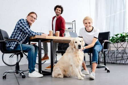young start up team and dog looking at camera in office