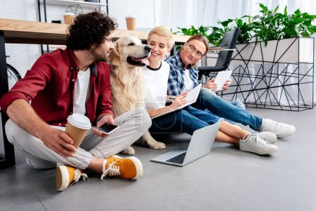 smiling young business colleagues looking at dog while working together in office