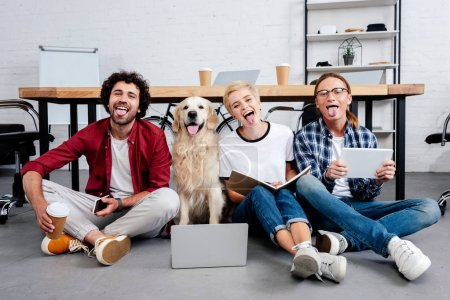 happy young business colleagues and dog sitting on floor with tongues out in office