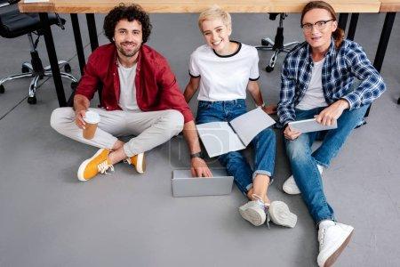 vista de ángulo alto de los jóvenes empresarios trabajando juntos y sonriendo a la cámara