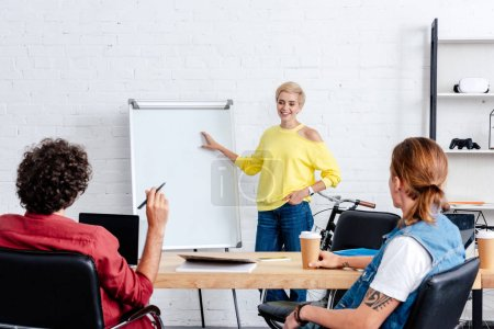 smiling young woman pointing at whiteboard and looking at male colleagues in office