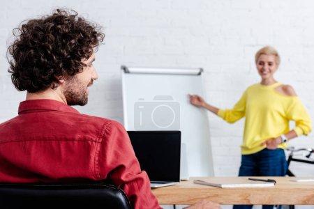 Photo pour Vue arrière du souriant jeune homme regardant collègue pointant sur tableau blanc - image libre de droit