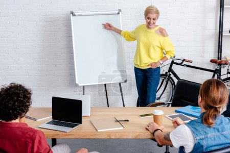 smiling young woman pointing at blank whiteboard and looking at male colleagues in office