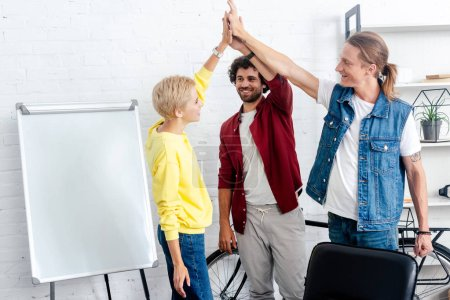 young start up team giving high five while working together neat whiteboard