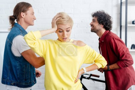 upset young woman looking down while male colleagues arguing behind