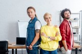 confident young business people standing together and smiling at camera in office