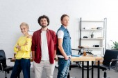 confident young business colleagues standing together and smiling at camera in office