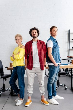 confident young business team standing together and smiling at camera in office