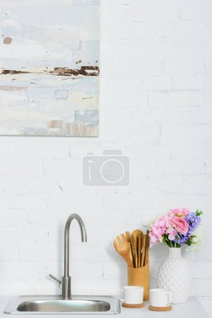 vase with colored flowers, cups and wooden utensil on kitchen counter near sink