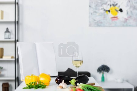 Photo for Vegetables and glass of wine on kitchen counter in light modern kitchen - Royalty Free Image