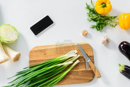 green onion on wooden board, smartphone with blank screen on white tabletop in kitchen