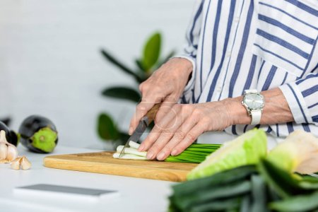 cropped image of grey hair woman cutting fresh green onion on wooden board in kitchen