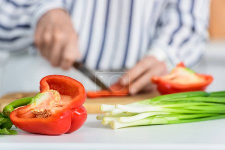 Photo for Cropped image of senior woman cutting red bell pepper on wooden board in kitchen with vegetables on foreground - Royalty Free Image