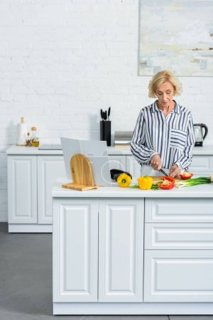 Photo for Attractive grey hair woman cooking in kitchen and cutting vegetables - Royalty Free Image