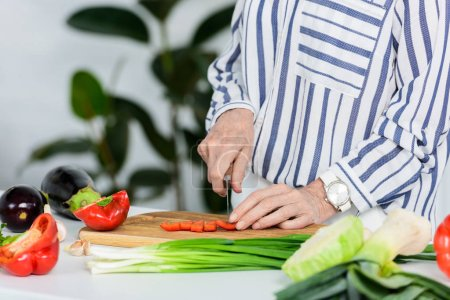cropped image of senior woman cutting red bell pepper on wooden board in kitchen
