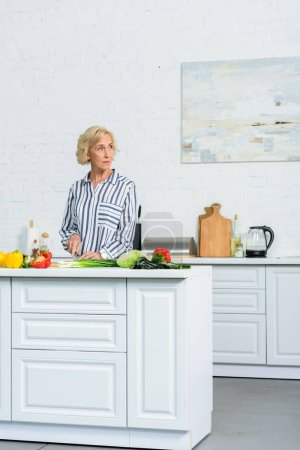 beautiful grey hair woman cutting vegetables in kitchen and looking away