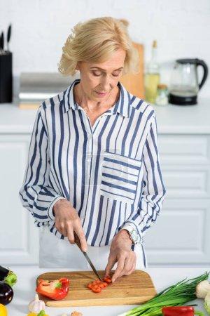jolie femme senior, couper le poivron rouge sur planche de bois dans la cuisine