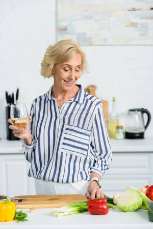 smiling attractive senior woman holding glass of white wine in kitchen and looking at vegetables