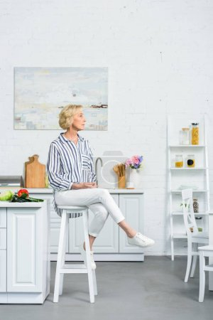 attractive grey hair woman sitting on high chair in kitchen and looking away