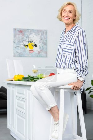 happy attractive grey hair woman sitting on high chair in kitchen