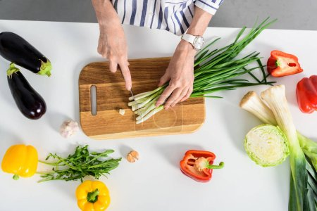 cropped image of senior woman cutting green onion in kitchen