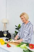 smiling attractive grey hair woman cutting leek on wooden board in kitchen