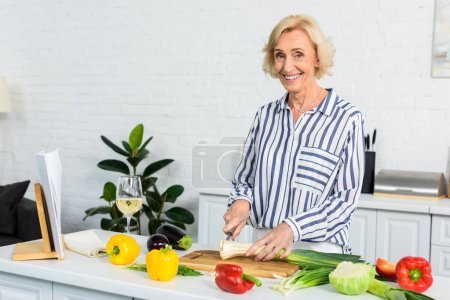 Photo for Smiling grey hair woman cutting leek on wooden board in kitchen and looking at camera - Royalty Free Image