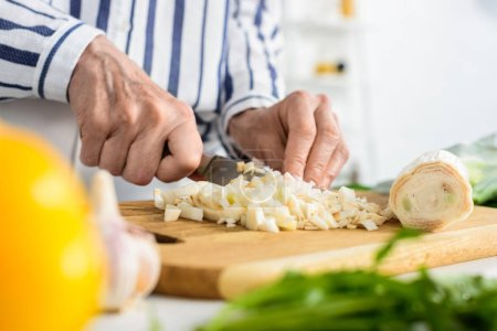Photo for Cropped image of grey hair woman cutting leek on wooden board in kitchen - Royalty Free Image