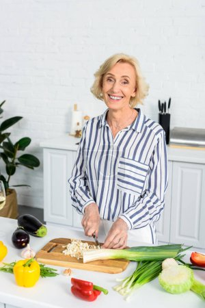 Photo for Smiling attractive senior woman cutting leek on wooden board in kitchen and looking at camera - Royalty Free Image