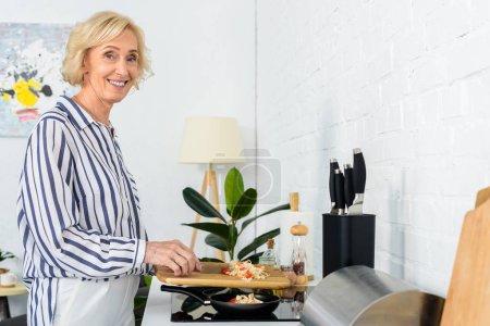 Photo pour Vue latérale de sourire belle femme âgée mettant des légumes sur la poêle dans la cuisine - image libre de droit