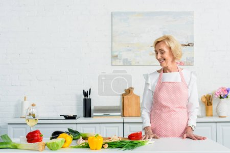 Photo for Smiling attractive senior woman standing at kitchen counter and looking at vegetables - Royalty Free Image