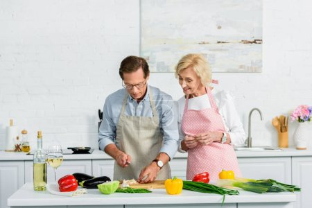 senior wife looking how husband cutting vegetables at kitchen