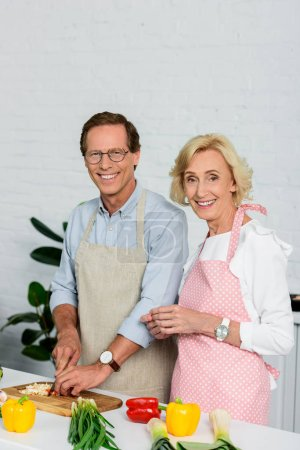 smiling senior couple cooking together at kitchen and looking at camera