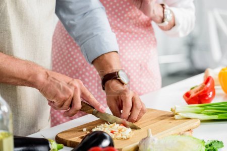 cropped image of senior husband cutting vegetables on wooden board at kitchen